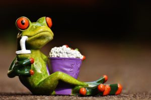 frog watching a movie with popcorn